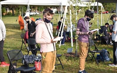 Students at the Ida Crown Jewish Academy pray in an outdoor service while wearing masks and maintaining social distance. The school has reopened with strict COVID protocols. (Ezra Landman-Feigelson via JTA)