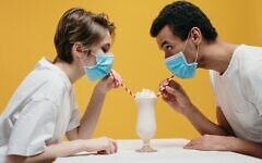 Couple wearing face masks and drinking a milkshake (Photo by cottonbro via Pexels)