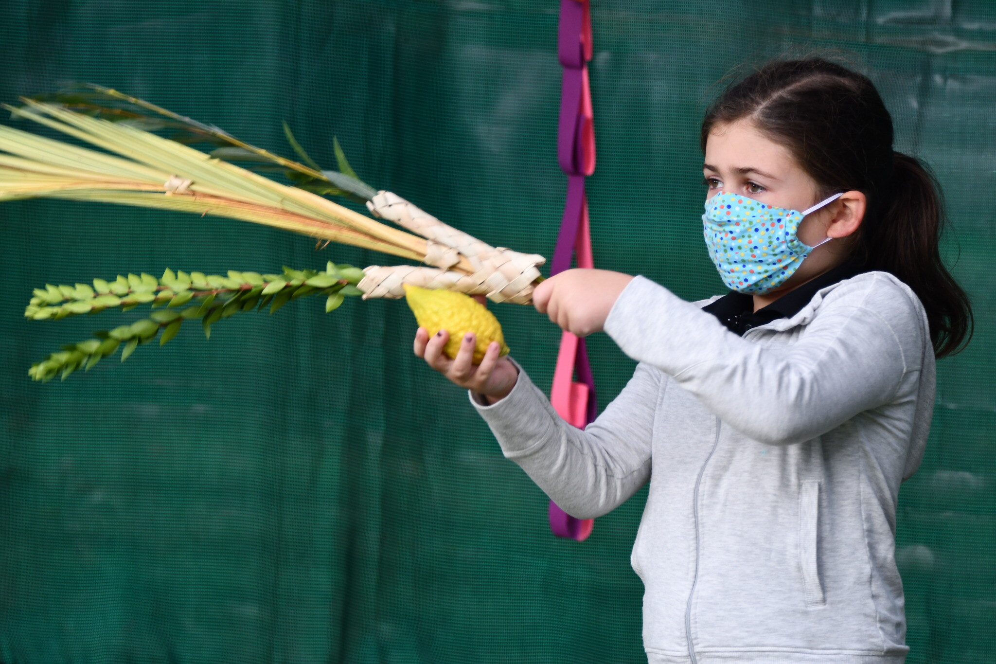 CDS first grader Tatum Baron shakes a lulav and etrog. Photo courtesy of Community Day School