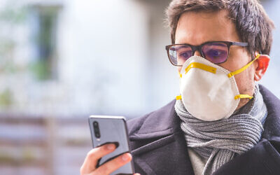 Young business man outdoors with a breathing mask and smartphone. Flue and corona season. Photo by Patrick Daxenbichler/iStockphoto.com