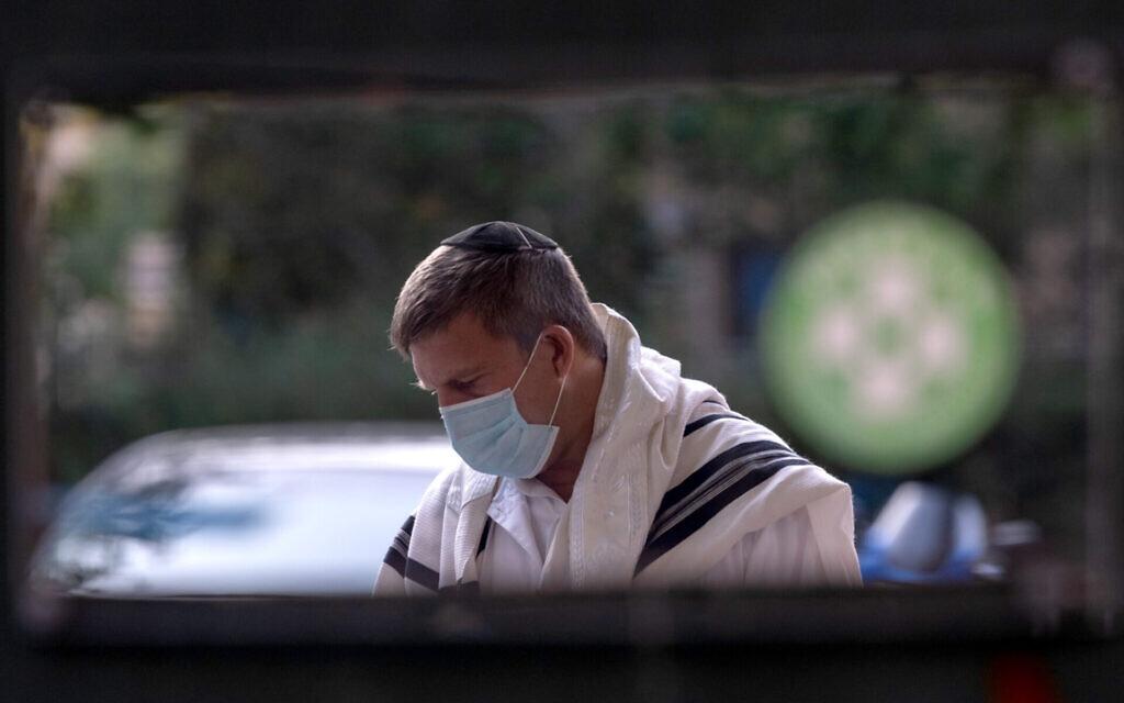An Orthodox Jewish man wearing a mask prays at an outdoor Yom Kippur service on New York City's Upper West amid the coronavirus pandemic, Sept. 28, 2020. (Alexi Rosenfeld/Getty Images via JTA)
