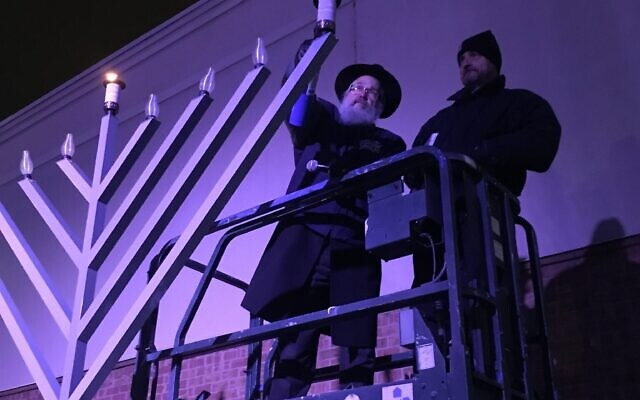 Rabbi Yisroel Rosenfeld lights the menorah at last year's Chanukah celebration at the Waterfront. Due to COVID-19 concerns, large public holiday events have been put on hold until next year. Photo provided by Rabbi Yisroel Altein