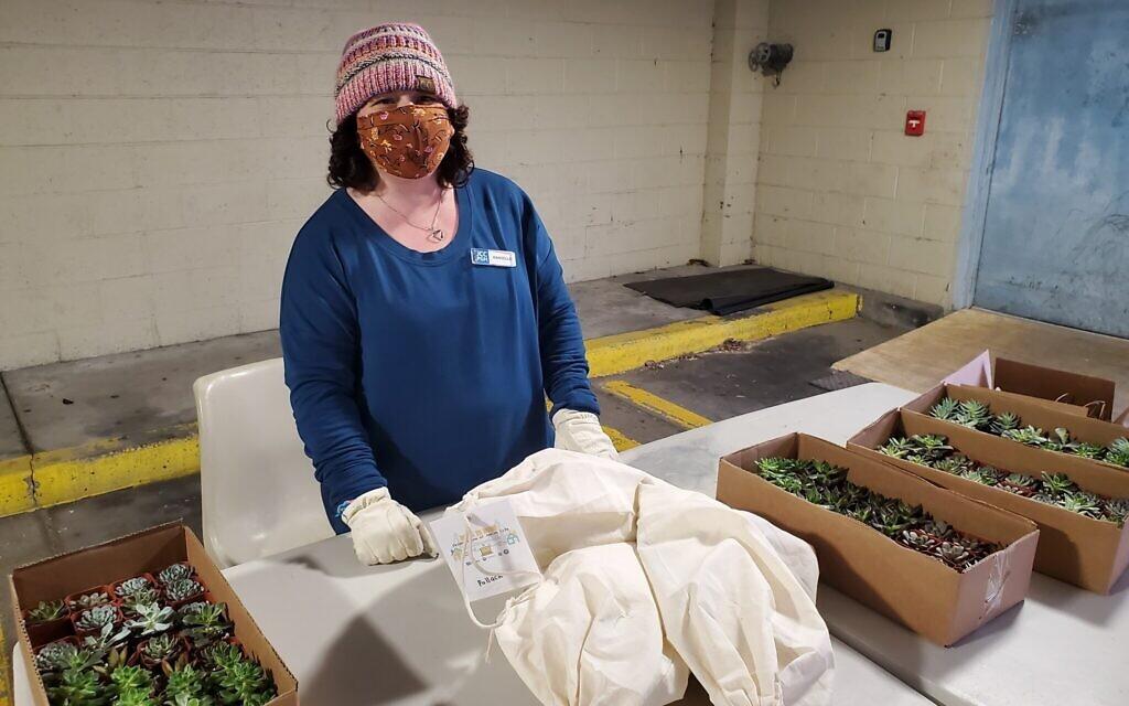 Danielle West distributes kits for the Tu B'Shevat Terrariums program. Photo by Adam Reinherz