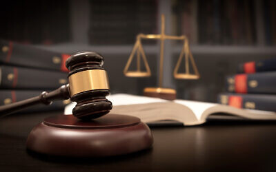 Judge gavel and scale in court. Library with lot of books in background. Photo by simpson33 via iStock