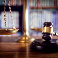 Judge gavel, scales of justice and law books in court. Photo by BrianAJackson via iStock