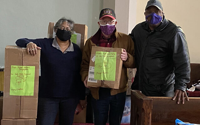 From left: Sylvia Wilson, Church of the Holy Cross Episcopal; Salem Leaman, Rodef Shalom Congregation; and Rev. Torrey Johnson, Church of the Holy Cross Episcopal with boxes of donated toys (Photo by Carol Leaman)