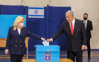 Benjamin Netanyahu casts his vote, together with his wife Sara Netanyahu at a voting station in Jerusalem, during the Knesset Elections, on March 23, 2021. (Photo by Marc Israel Sellem/POOL via JTA)