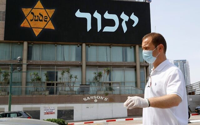"""A banner depicting a yellow star of David and """"Remember"""" in Hebrew is seen in Tel Aviv on April 21, 2020. (Photo by JACK GUEZ/AFP via Getty Images via JTA)"""