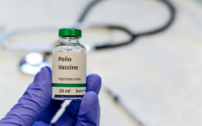 Poliomyelitis virus vaccine with stethoscope and syringe at the background. Photo by Manjurul via iStock