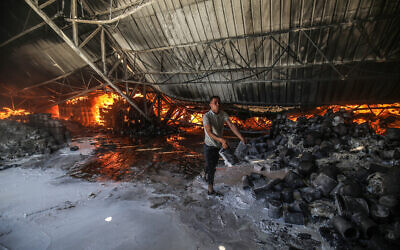 Firefighters attempt to extinguish a fire at a warehouse which was hit during an Israeli airstrike in Rafah, in the southern Gaza Strip, on May 18, 2021. (Photo by Abed Rahim Khatib/Flash90 via JTA)