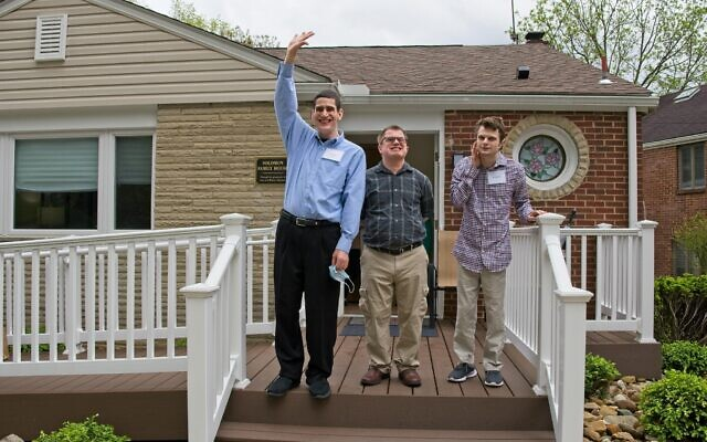 David Wilf, left, Jeremy White and Michael Fox stand outside their new residence.  Photo by Don Koch
