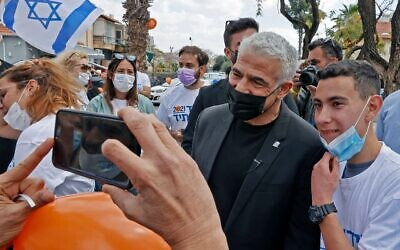 Yair Lapid (C) campaigns in the coastal Mediterranean city of Hod Hasharon on March 19, 2021. (Photo by JACK GUEZ/AFP via Getty Images via JTA)