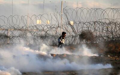 A Palestinian demonstrator walks amid tear gas smoke fired by Israeli forces during a protest near the Israel-Gaza border fence, Dec. 27, 2019. (Photo by Said Khatib/AFP via Getty Images via JTA)