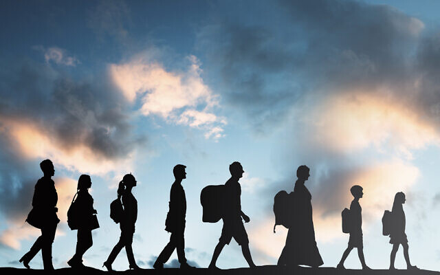 Silhouette of refugees walking in a row. Photo by AndreyPopov via iStock