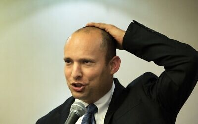 Israeli Prime Minister Naftali Bennett, pictured giving a speech when he was economy minister in 2014, holds his kippah to his head. (Menahem Kahana/AFP via Getty Images)