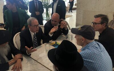 Nachman Shai, second from left, speaks to Sen. Rick Scott, in cap, at the Grand Beach Hotel in Surfside, Fla., June 27, 2021. (Ron Kampeas)