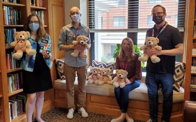 Lauren Apter Bairnsfather, Light Education Initiative program Nick Haberman, Shadyside Family House Associate House Manager Rebekah Little  and Dorseyville Middle School teacher Scott Vensel hold donated Teddy Bears and a note handwritten by a student. Photo provided by Scott Vensel.