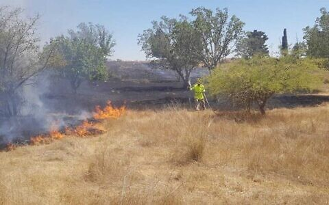Fire and rescue services put out a fire allegedly sparked in the Western Negev by arson balloons launched by Gaza terrorists, June 16, 2021. (Itzik Lugasi/KKL-JNF via The Times of Israel)