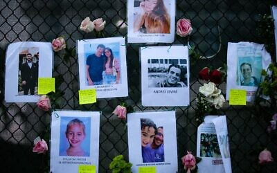 Images of Andres Levine, Ilan Naibryf and Deborah Berezdivin, three of the Jewish victims of the Surfside building collapse, in center among other photographs of those missing posted at a makeshift memorial on the building site in Surfside, Fla., June 26, 2021. (Andrea Sarcos/AFP via Getty Images)