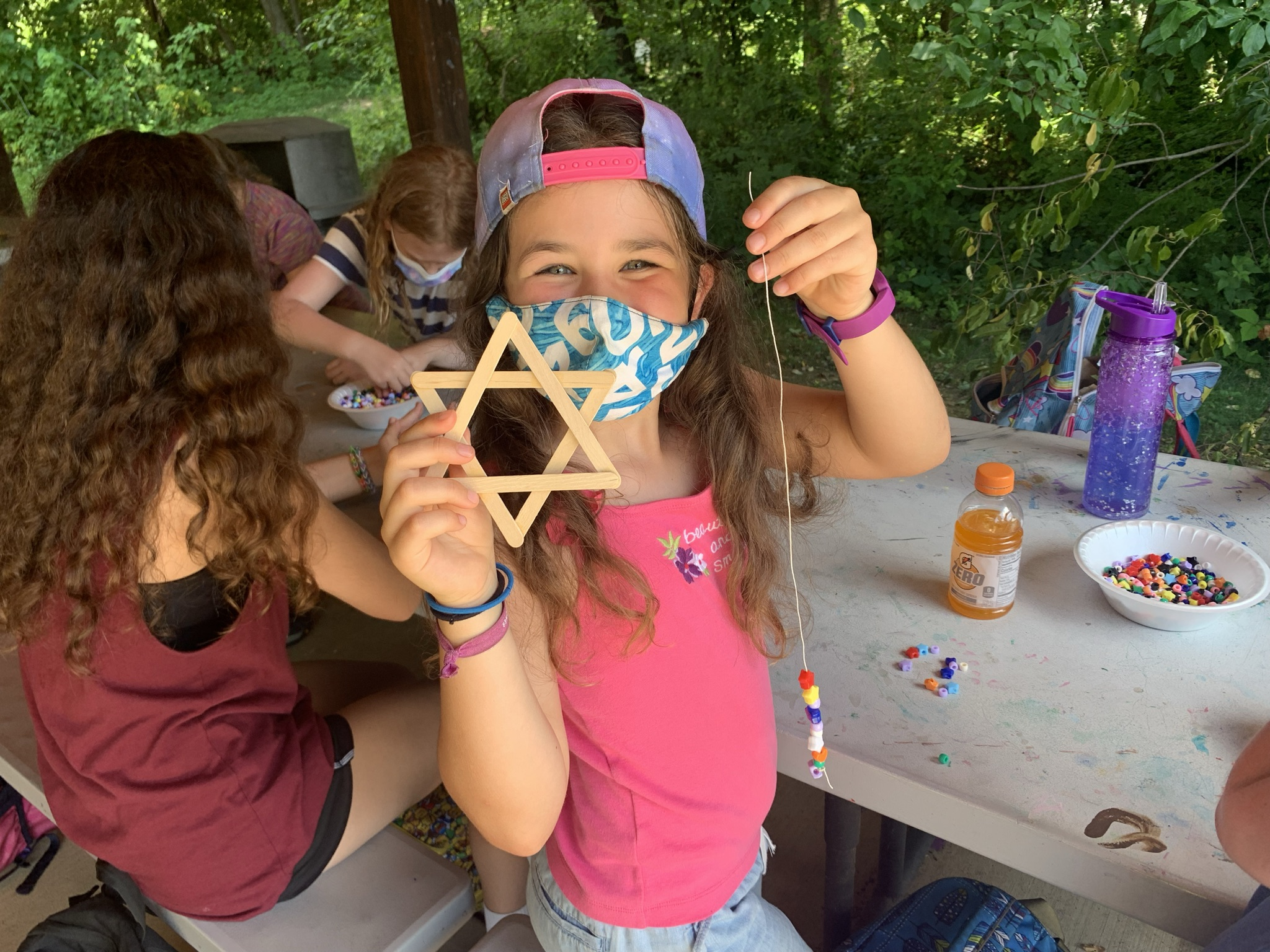 Camper enjoys the classic outdoor summer pairing of popsicle sticks and beading at J&R Day Camp. Photo courtesy of Emma Curtis via Jewish Community Center of Greater Pittsburgh