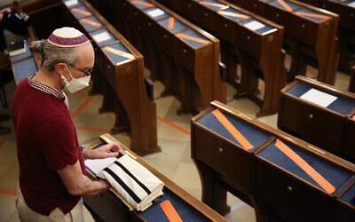 A congregation member packs his tallit, or prayer shawl, after attending socially-distant morning prayer services at the Stadttempel synagogue as the pandemic continues, on June 23, 2021, in Vienna, Austria. (Photo by Adam Berry/Getty Images via JTA)