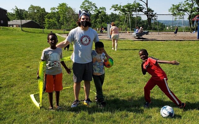 Volunteer Joe Rokicki and children at a JFCS Newcomers Crew event. Photo courtesy of JFCS