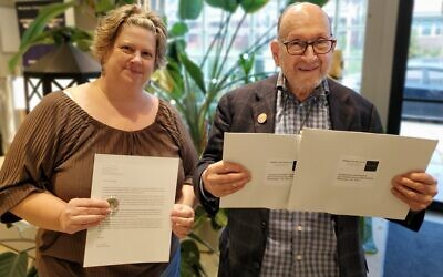 Tracy Kosylo and Irwin Kotovsky hold a commemorative coin, letter and envelopes. Photo by Adam Reinherz