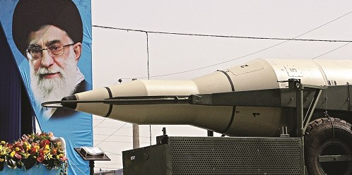 A missile is displayed by Iran's Revolutionary Guard, in front of a portrait of the Iranian supreme leader Ayatollah Ali Khamenei.