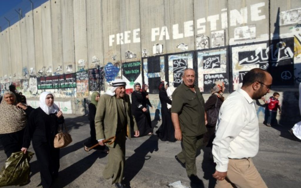 Palestinians next to the West Bank security barrier that separates them from Israel