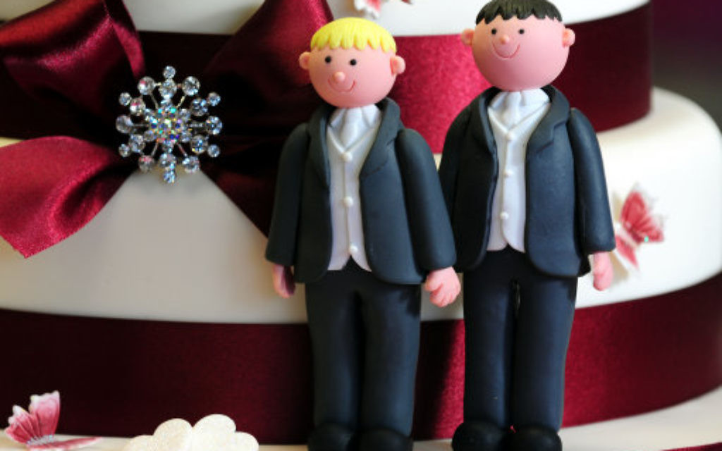 Two grooms decorating a wedding cake.