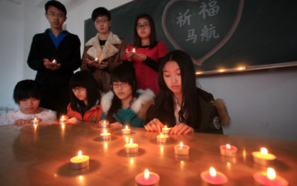 College students light candles to pray for the missing passengers