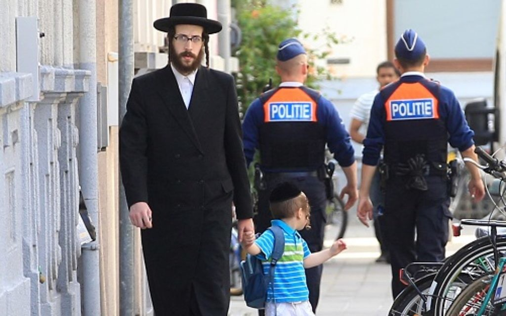 An orthodox Jew and a boy pass two police officers in Antwerp, Belgium,   2014.  (AP Photo/Yves Logghe)