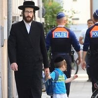 An orthodox Jew and a boy pass two police officers in France