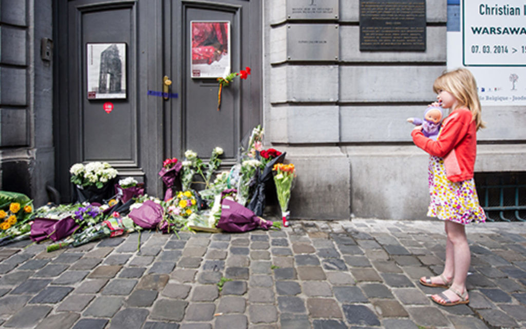 A girl stands next to flowers at the Jewish Museum in Brussels. Photo: AP