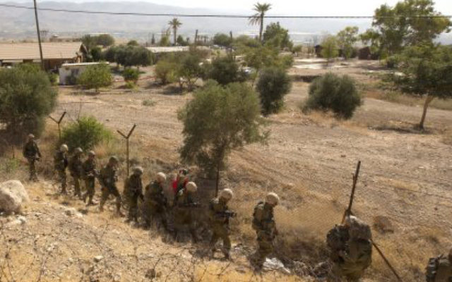 Israeli soldiers patrol a fence in the West Bank.