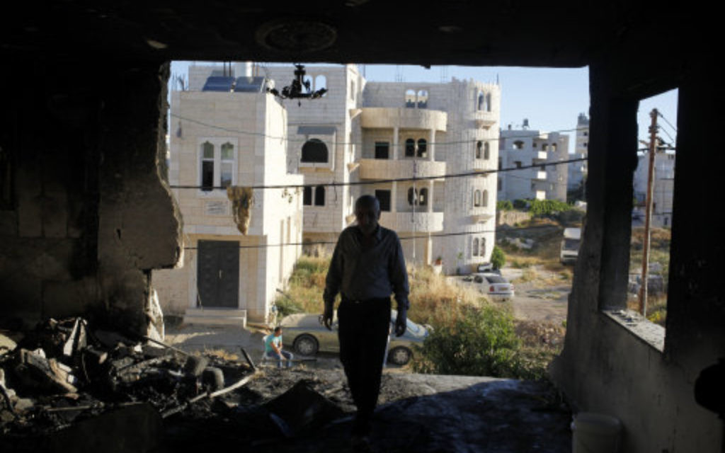 A Palestinian inspects the damaged family home of Amer Abu Aisheh, one of two Palestinians identified  as suspects in the killing of the three Israeli teenagers.