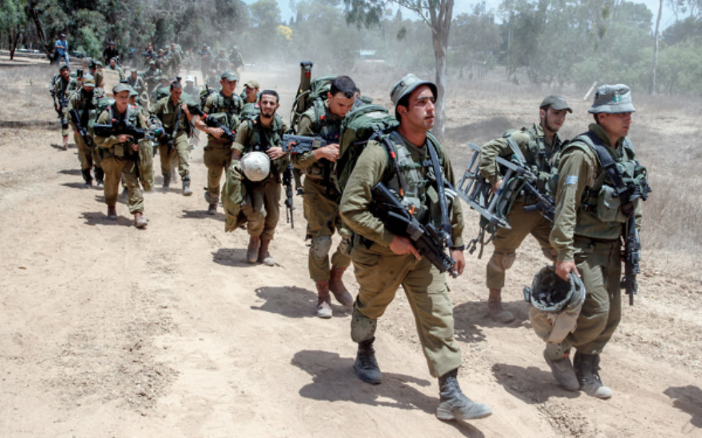 Israeli combat soldiers carry their gear as they walk towards a staging area before entering the Gaza strip. Photo: Jinipix/Israel Sun