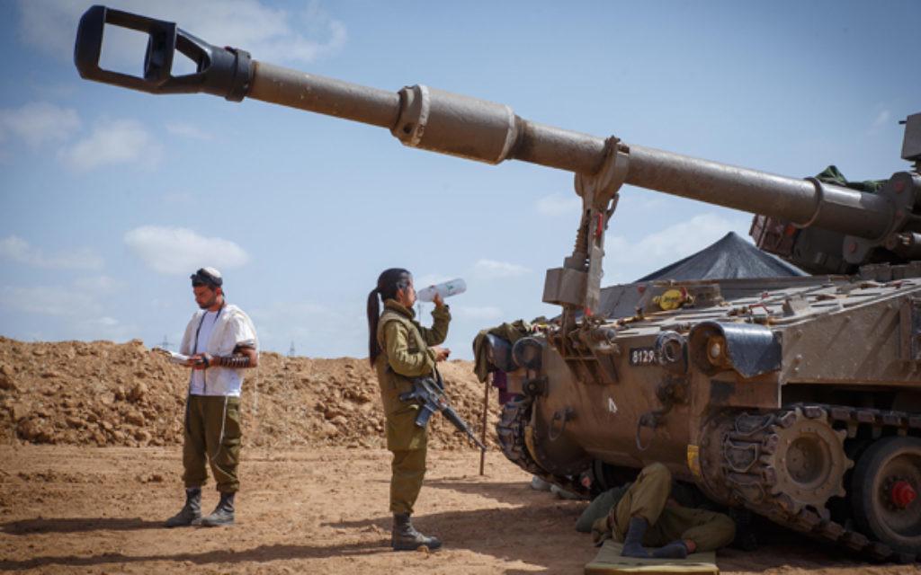 An Israeli soldier prays along the southern Israeli border.
