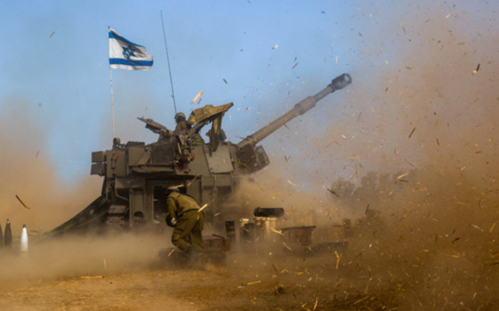 Israeli soldiers on a 155mm M109 Dores self-propelled howitzer fire a shell towards Gaza.