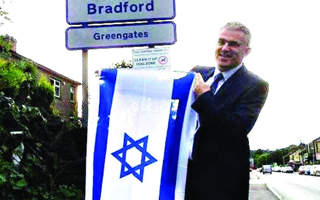 Ambassador Taub holding the Israeli flag on a visit to Bradford last week
