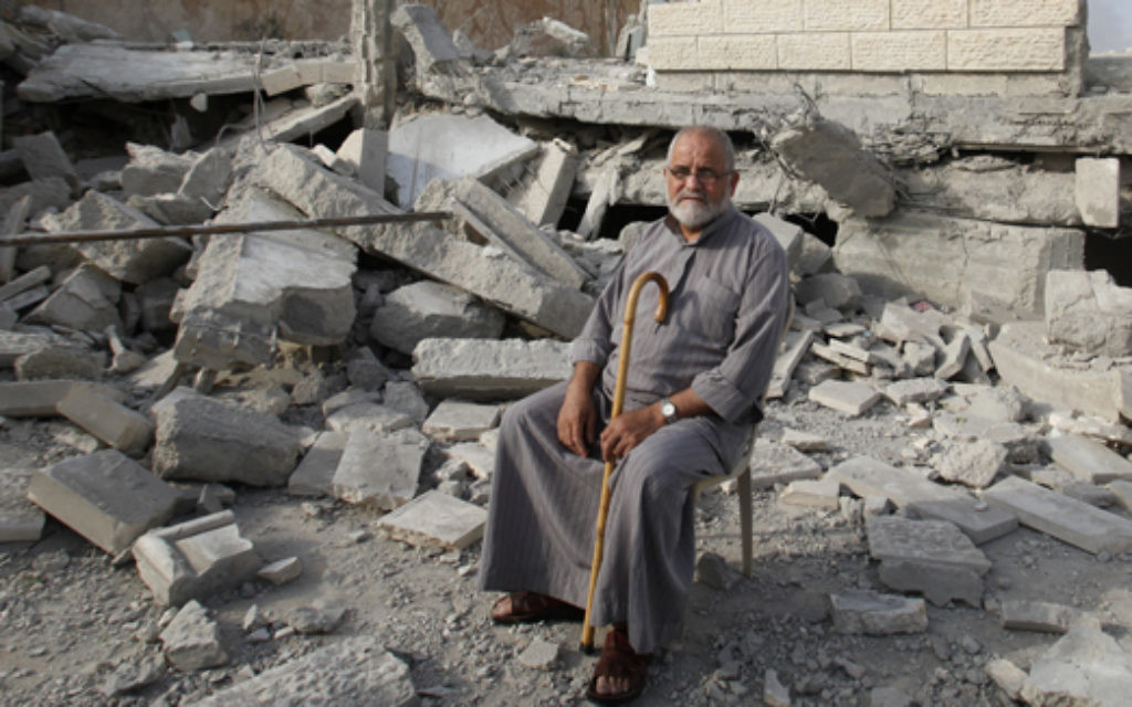 A Palestinian sits in the rubble of the house of Hussam Kawasma, one of three Palestinians identified by Israel as suspects in the killing of three Israeli teenagers, after it was demolished by the Israeli army in the West Bank city of Hebron, Monday, Aug. 18 , 2014. Troops also demolished the home of another militant suspected in the abduction and killing of the teens, whose deaths sparked the war in Gaza, and sealed up the home of a third. (AP Photo/Nasser Shiyoukhi)