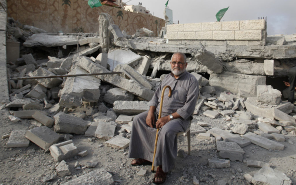 A Palestinian sits in the rubble of the house of Hussam Kawasma, one of three Palestinians identified by Israel as suspects in the killing of the three kidnapped Israeli teenagers.