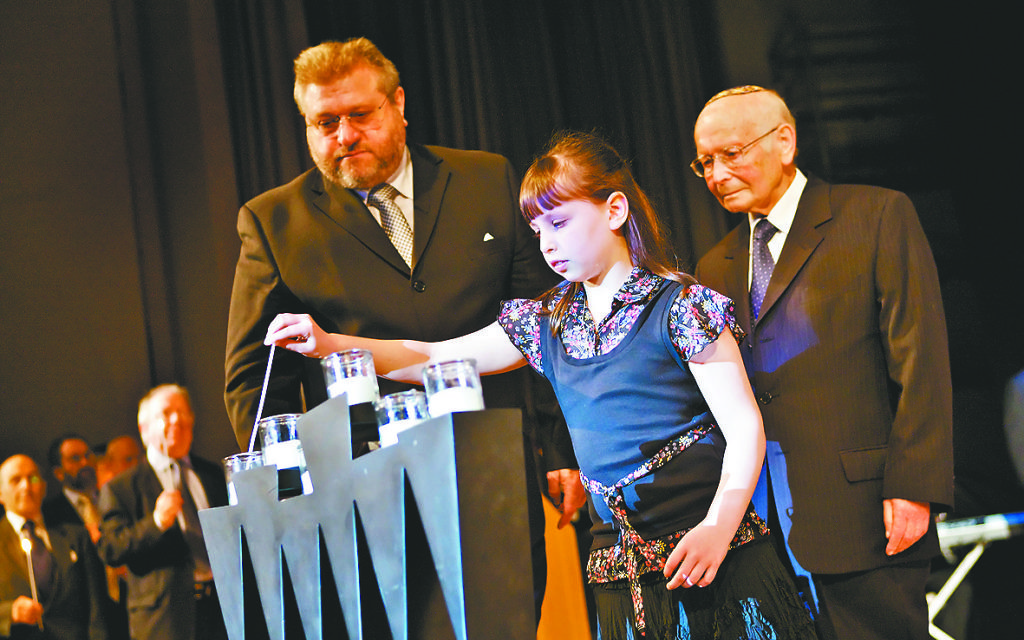 A girl lights memorial candles at a Yom Hashoah ceremony