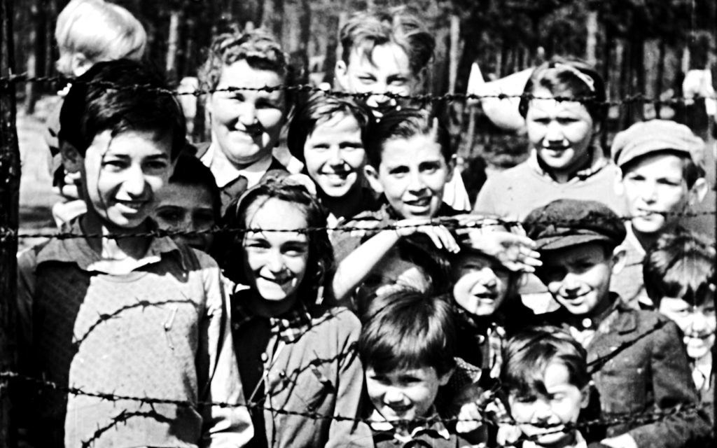 Night will fall pic (credit IWM) children smiling through barbed wire