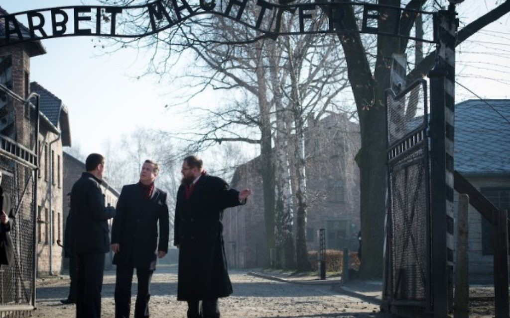 Prime Minister David Cameron stands under the entrance gates to Auschwitz, during a visit to the former Nazi death camp in Poland, where he has made his visit since becoming Prime Minister. PRESS ASSOCIATION Photo. Picture date: Wednesday December 10, 2014. The Prime Minister is travelling to the notorious site on the way back from Turkey, where he held talks with President Recep Tayyip Erdogan. See PA story POLITICS Cameron. Photo credit should read: Stefan Rousseau/PA Wire