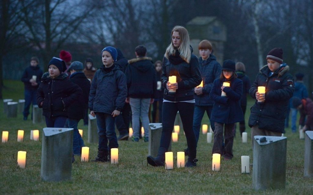 Children bring candles to at a Jewish cemetery at the former Terezin Nazi concentration camp on January 27, 2015, in Terezin (Theresiendstadt ) during the ceremony to mark the 70th anniversary of the liberation of the former Nazi concentration camp Auschwitz-Birkenau in Oswiecim, Poland. AFP PHOTO / MICHAL CIZEK        (Photo credit should read MICHAL CIZEK/AFP/Getty Images)