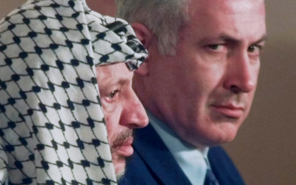 Israeli Prime Minister Benjamin Netanyahu, right, looks around PLO leader Yasser Arafat in 1996.