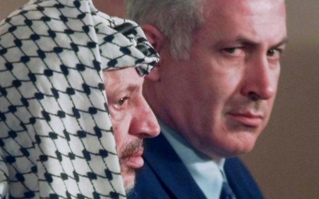 Israeli Prime Minister Benjamin Netanyahu, right, looks around PLO leader Yasser Arafat in 1996.