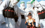 Hamas terrorists surround a child dressed as a suicide bomber.