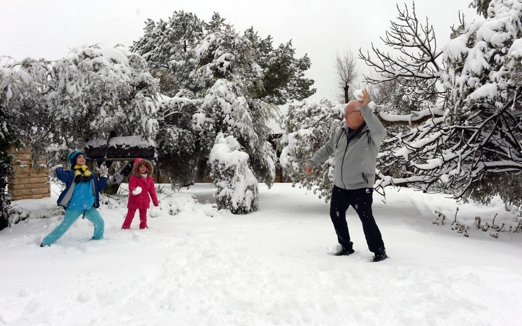 Israeli President Reuven Rivlin plays with granddaughters Karni and Ziv in the snow that covered his Jerusalem residence's garden.